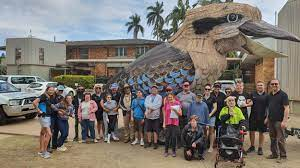 A group of people posing for a photo in front of a Giant Kookaburra.